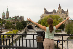 Young woman tourist with arms up, back to camera in Ottawa, Cana Stock Photo