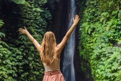 Young woman tourist on the background of Leke Leke waterfall in Bali island Indonesia.  royalty free stock images
