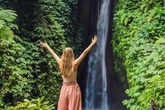 Young woman tourist on the background of Leke Leke waterfall in Bali island Indonesia.  royalty free stock image
