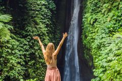 Young woman tourist on the background of Leke Leke waterfall in Bali island Indonesia.  royalty free stock photography