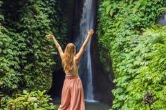 Young woman tourist on the background of Leke Leke waterfall in Bali island Indonesia.  stock photography