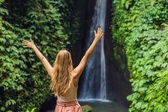 Young woman tourist on the background of Leke Leke waterfall in Bali island Indonesia.  stock photos