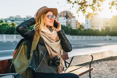 Young woman tourist with backpack and camera sits on bench in city street and talks on her cell phone. Girl using gadget. Sunny day.Young woman tourist with Royalty Free Stock Image
