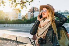 Young woman tourist with backpack and camera sits on bench in city street and talks on her cell phone. Girl using gadget. Sunny day.Young woman tourist with Royalty Free Stock Images