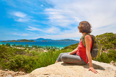 Young woman tourist with backpack sit on a rock on clear sky bac Stock Photo