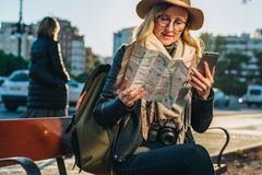 Young woman tourist with backpack sits on bench in city street, looks at map and holding smartphone. Vacation, travel. Young woman tourist with backpack and Royalty Free Stock Photo