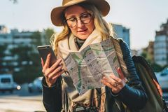 Young woman tourist with backpack sits on bench in city street, looks at map and holding smartphone. Vacation, travel. Young woman tourist with backpack and Stock Image