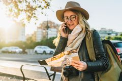 Young woman tourist with backpack sits on bench on street, looks at map and talks on her cell phone. Girl using gadget. Young woman tourist with backpack Royalty Free Stock Photos