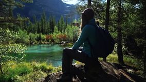 Young woman tourist with backpack is sitting on a stone and is enjoying the scenic view of the beautiful montain lake in. A sunny day 25 fps stock video footage