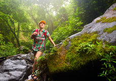 Young woman tourist with a backpack walking along the trail in t stock image