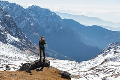 Young woman tourist backpacker standing rock mountain edge. Royalty Free Stock Image