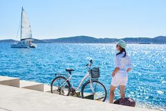 Young woman tourist biker with city bicycle in the town near the sea royalty free stock images