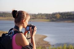 Young woman tourist with camera on nature. Young woman tourist with a digital camera makes the photo on nature Royalty Free Stock Photo