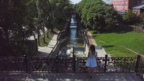 Young woman tourist enjoying beautiful landscape view on the old town. Clip. Top view of the girl standing on the bridge royalty free stock image
