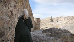 A young woman tourist in a green leather jacket walks alongside the fortress wall of an ancient monastery. Cross on the hill in front stock footage
