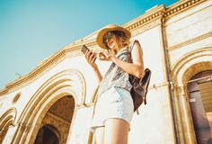 Young woman tourist in hat with backpack using gps navigation on phone. Online booking. Summer fashion style. City tour. Explore t Royalty Free Stock Photo