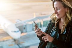 Woman tourist in hat sits at airport near window,uses smartphone.In background white airplane.Hipster girl checks email. Young woman tourist in hat sits at Royalty Free Stock Photos