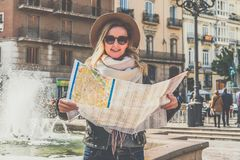 Young woman tourist in hat standing on street of beautiful European city near fountain and holding destination map. Young woman tourist in hat standing on Stock Image