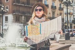 Young woman tourist in hat standing on street of beautiful European city near fountain and holding destination map. Young woman tourist in hat standing on Royalty Free Stock Photo