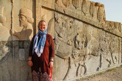 Young woman tourist with a head covered stands on the background of the famous bas-reliefs of the day capital of Persia Iran - P stock image