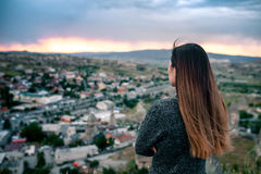 Young woman tourist from a high point looking at the sunset over the city of Goreme in Cappadocia in Turkey and dreaming Stock Photo