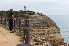 Young woman tourist hiking along the coast, Algarve region, Portugal Stock Photo