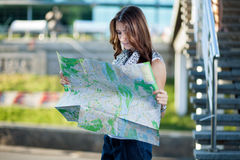 Young woman tourist holding paper map outdoors Stock Images