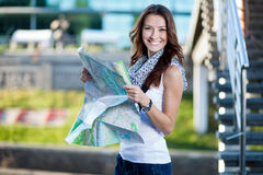Young woman tourist holding paper map outdoors Stock Photo
