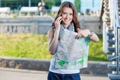 Young woman tourist holding paper map Stock Images