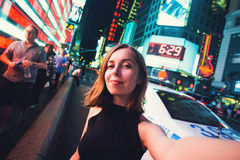 Young woman tourist laughing and taking selfie photo in New York City, Manhattan, Times Square. Female traveler and photographer takes selfie picture for her stock images