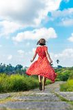 Young woman tourist in a lon red dress running on the rainforest trail. Bali island. Indonesia royalty free stock photos