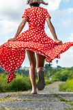 Young woman tourist in a lon red dress running on the rainforest trail. Bali island. Indonesia royalty free stock photo