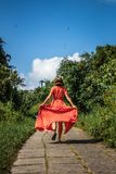Young woman tourist in a lon red dress running on the rainforest trail. Bali island. Indonesia royalty free stock images