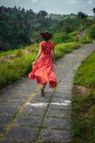Young woman tourist in a lon red dress running on the rainforest trail. Bali island. Indonesia stock photography