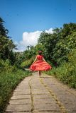 Young woman tourist in a lon red dress running on the rainforest trail. Bali island. Indonesia stock photos