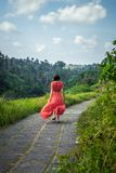 Young woman tourist in a lon red dress running on the rainforest trail. Bali island. Indonesia stock photo
