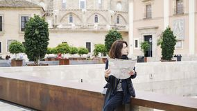 Young woman tourist is looking at a map in a street in Valencia, Spain, Europe. Portrait of a young and beautiful woman looking at a map she is holding. Valencia stock video footage