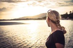 Young woman tourist looking into the sea horizon during beautiful sunset during summer beach holidays. Lonely young woman tourist looking into the sea horizon Stock Photo