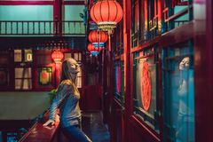 Young woman tourist looks at the Chinese traditional lanterns. Chinese New Year. Travel to China concept stock image