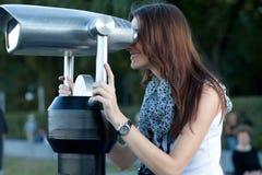 Young woman tourist looks through a telescope Stock Photos