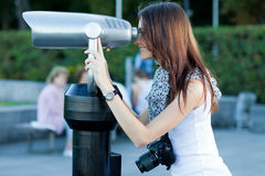 Young woman tourist looks through a telescope Stock Photo