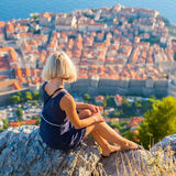 Young woman tourist looks to the old city of Dubrovnik. Royalty Free Stock Image