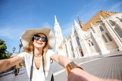 Woman traveling in Budapest. Young woman tourist making selfie photo standing in front of the famous Mattias church in Budapest, Hungary stock image