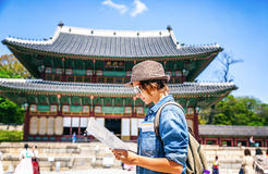 Young woman tourist with map in hand on the background of Asian stock images