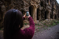 Young woman tourist photographing old ruins Stock Images