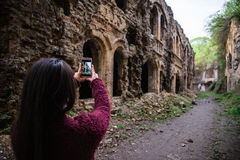 Young woman tourist photographing old ruins Stock Photo