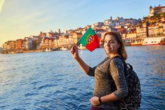 Young woman tourist with portuguese flag enjoying beautiful landscape view on the old town Ribeira historical quarter and river royalty free stock photos