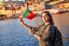 Young woman tourist with portuguese flag enjoying beautiful landscape view on the old town Ribeira historical quarter and river royalty free stock photo