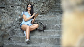 Young woman tourist is reading interesting historical facts on touch pad during a tour in the old town. stock video footage