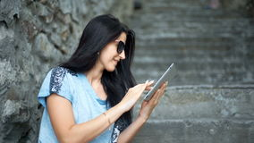 Young woman tourist is reading interesting historical facts on touch pad during a tour in the old town. stock video